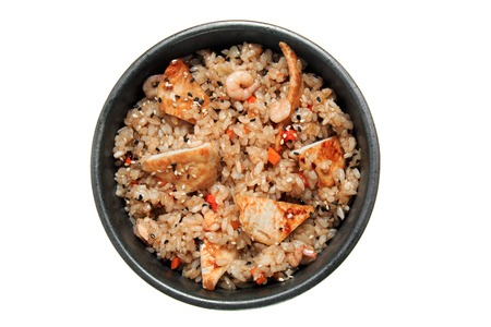 Rice with fried chicken, shrimps, vegetables and sesame in the black bowl. Isolated on white background. Tasty restaurant dish.