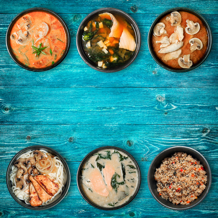 Traditional Asian dishes in black bowls. Wooden blue background with copy space. View from the top.