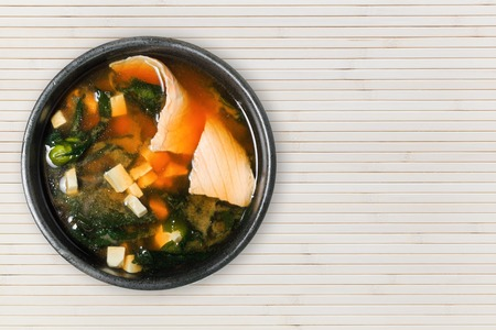 Appetizing soup with salmon, tofu and seaweed. Wooden background with copy space. Asian cuisine. Banque d'images - 125394803
