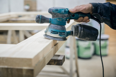 Worker sanding the wooden surface. In the hand of the power tool. Banque d'images - 125518634