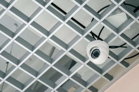 Surveillance camera on the lattice ceiling. Modern technologies.