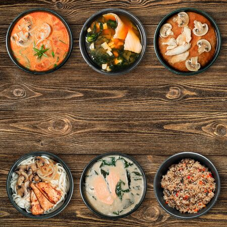 Tasty Asian dishes in black bowls. Wooden brown background with copy space. View from the top. Banque d'images - 130710883