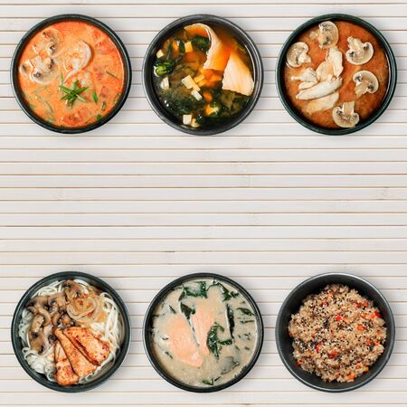 Delicious Asian dishes in black bowls. Wooden background with copy space. View from the top.