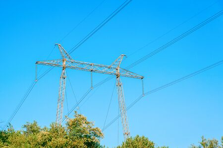 Metallic electrical tower transmitting high voltage. Energy industry. Banque d'images - 130710888
