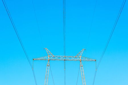 Metallic electrical tower transmitting high voltage. Energy industry. Banque d'images - 130710890