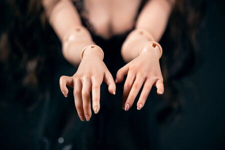 Hinged doll on a black background. Beautiful female hands closeup Stockfoto
