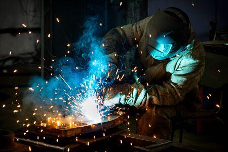 Spawacz pracuje z produktem metalowym. Piękne iskry w ciemności