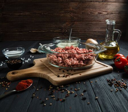 Raw minced meat with ingredients on black wooden boards. Homemade.