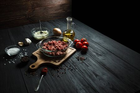 Raw minced meat with ingredients on a black wooden table. Home cooking.