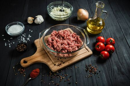 Raw minced meat with ingredients on a black wooden table. Homemade.