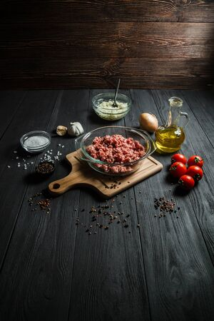 Raw minced meat with ingredients on black wooden boards. Home cooking.