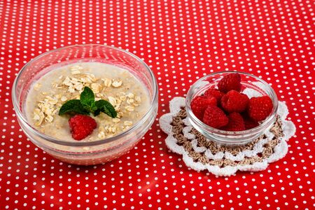 Oatmeal porridge with raspberries and mint leaves. Red background with white dots.