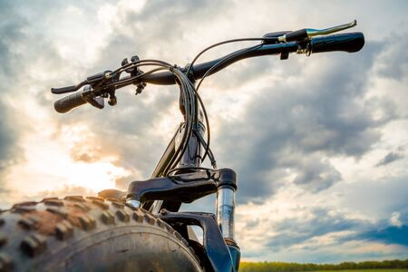 A Bicycle with thick wheels against a beautiful sky. Fatbike.