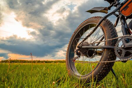 A Bicycle with thick wheels equipped with an electric motor. Fatbike against a beautiful sky. Stockfoto