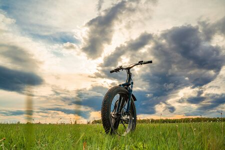 A Bicycle with thick wheels on a green meadow against a beautiful sky. Fatbike.