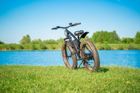 Electric bike with thick wheels near the lake. A pleasant sports hobby that allows you to travel. Fatbike.