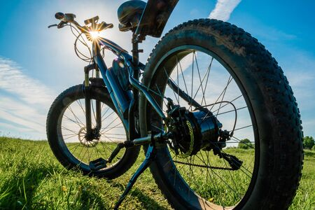 Electric bicycle with thick wheels in nature. Fatbike close-up.