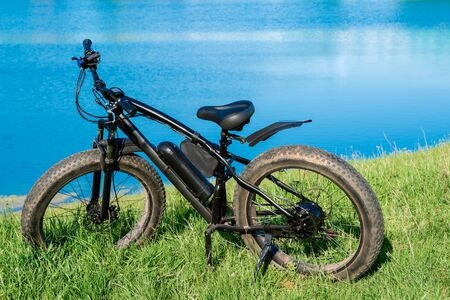 Black electric bike with thick wheels on the grass near the lake. Fatbike.