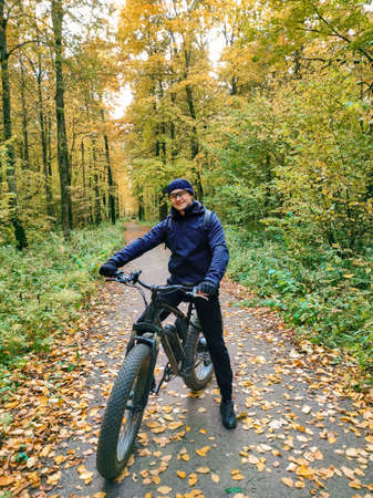 A sporty man on an electric fat bike in the woods. Super hobby. Ecological transport.