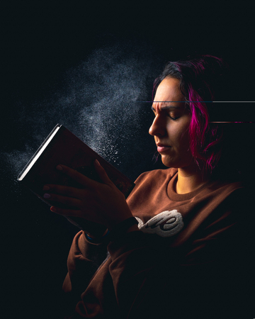 young woman slapping a dusty book on black background low key portrait