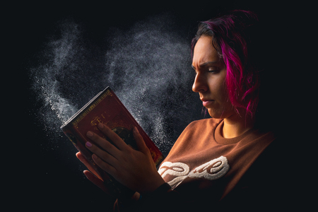 young angry woman slapping a dusty book on black background low key portrait 版權商用圖片