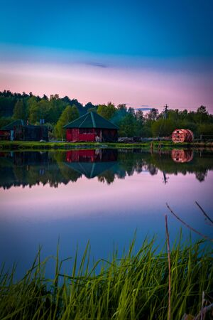 Small village red house with smoke of bonfire reflects in clearly blue still water at evening after sunset