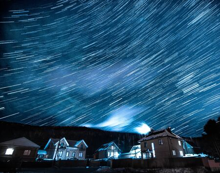Winter landscape with star trails above houses and forest at starry night