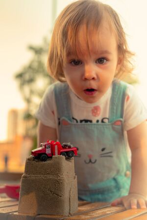 Little smiling girl playing with sand castle and red car toy in sandbox in summer