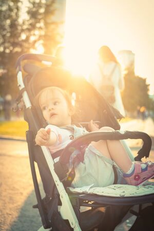 Restless little girl in baby carriage curious looking around in summer 写真素材