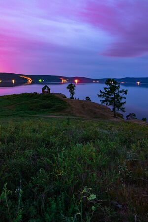 Beautiful long exposure landscape view of the mountain lake Turgoyak, Russia with purple sky and summer house on the hill in summer night 写真素材