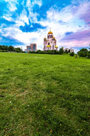 Wide angled view of the church Temple On The Blood in Yekaterinburg, Russia with beautiful cloudy sky and green grass on the foreground