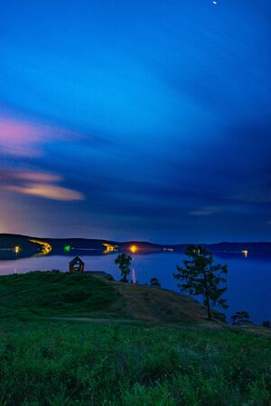 Beautiful long exposure landscape view of the mountain lake Turgoyak, Russia with cloudy sky and summer house on the hill in summer night