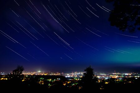 Star trails in clear night sky above the city with many lights view from mountain 写真素材