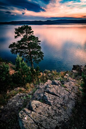 Beautiful sunset landscape on mountain lake with rocks and pine on the foreground 写真素材