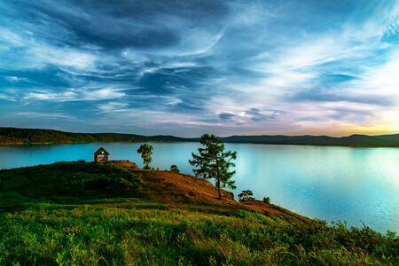 Beautiful landscape view of the mountain lake Turgoyak, Russia with cloudy sky and summer house on the hill in summer
