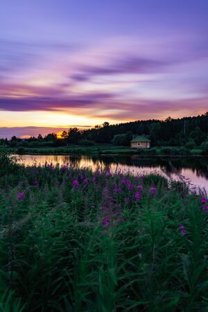 Beautiful long exposure landscape at sunset with purple sky and flowers and lonely little house at the bank of small pond