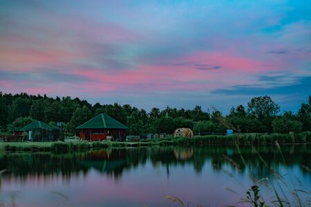 Long exposure scenic view of small red house on the bank of still pond reflecting beautiful blue and pink clouds after sunset