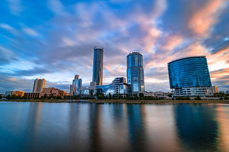 Beautiful wide angle long exposure cityscape of Yekaterinburg city, Russia at sunset with blurred blue and purple clouds. Skyscrapers reflecting in water of Iset river