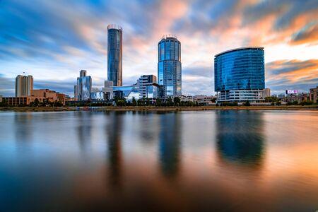 Schönes Weitwinkel-Langzeitbelichtungs-Stadtbild der Stadt Jekaterinburg, Russland bei Sonnenuntergang mit unscharfen blauen und violetten Wolken. Wolkenkratzer spiegeln sich im Wasser des Flusses Iset