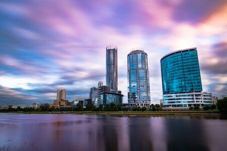 Piękny szeroki kąt długiej ekspozycji gród miasta Jekaterynburg, Rosja o zachodzie słońca z niewyraźne chmury niebieski i fioletowy. Drapacze chmur odbijające się w wodzie rzeki Iset