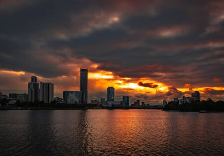 Cloudy sunset over Yekaterinburg business center reflecting in water of city pond 写真素材