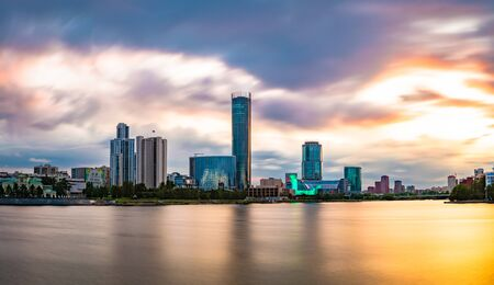 Beautiful panorama of Yekaterinburg city, Russia at sunset. Skyscrapers reflecting in water of Iset river 写真素材