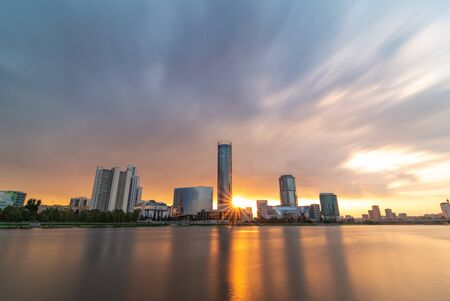 Beautiful cloudy sunset at the city pond. Long Exposure cityscape of Yekaterinburg, Russia with skyscrappers reflecting in water