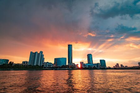 Beautiful cloudy sunset at the city pond. Cityscape of Yekaterinburg, Russia with skyscrappers reflecting in water 写真素材