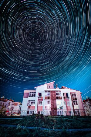Circle star trails in the night sky above the suburb houses
