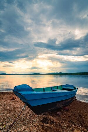Blue boat moored on the shore of lake under cloudy sky at sunset