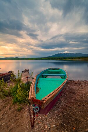 Green boat moored on the shore of lake under cloudy sky at sunset