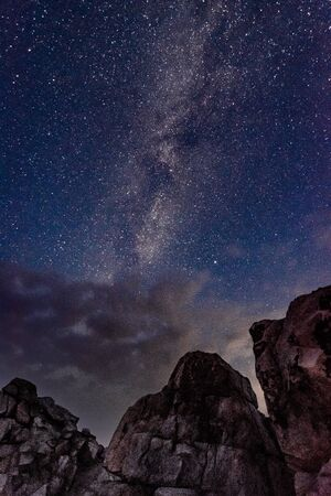 View of the milky way galaxy in the blue sky above the clouds and rocks