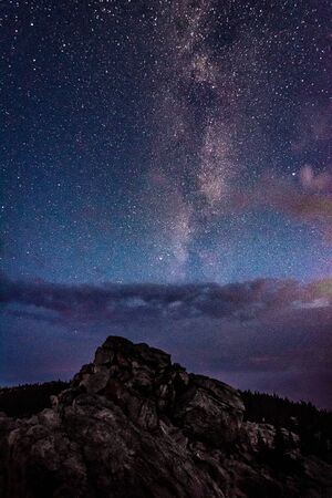 Milky Way galaxy in the night sky above rocky mountain and stormy clouds 写真素材