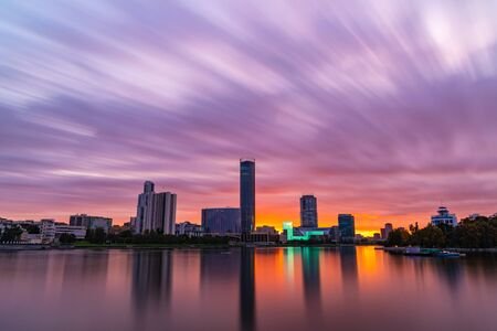 Beautiful purple and orange cloudy sunset at the city pond. Long Exposure cityscape of Yekaterinburg, Russia with skyscrappers reflecting in water 写真素材